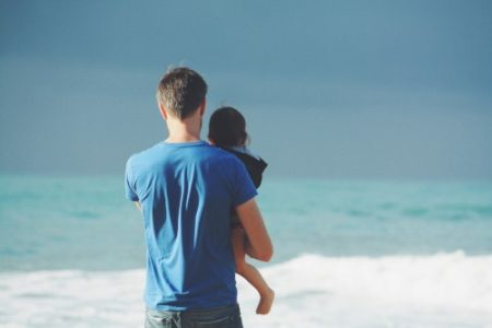 Man holding daughter at the beach in family case